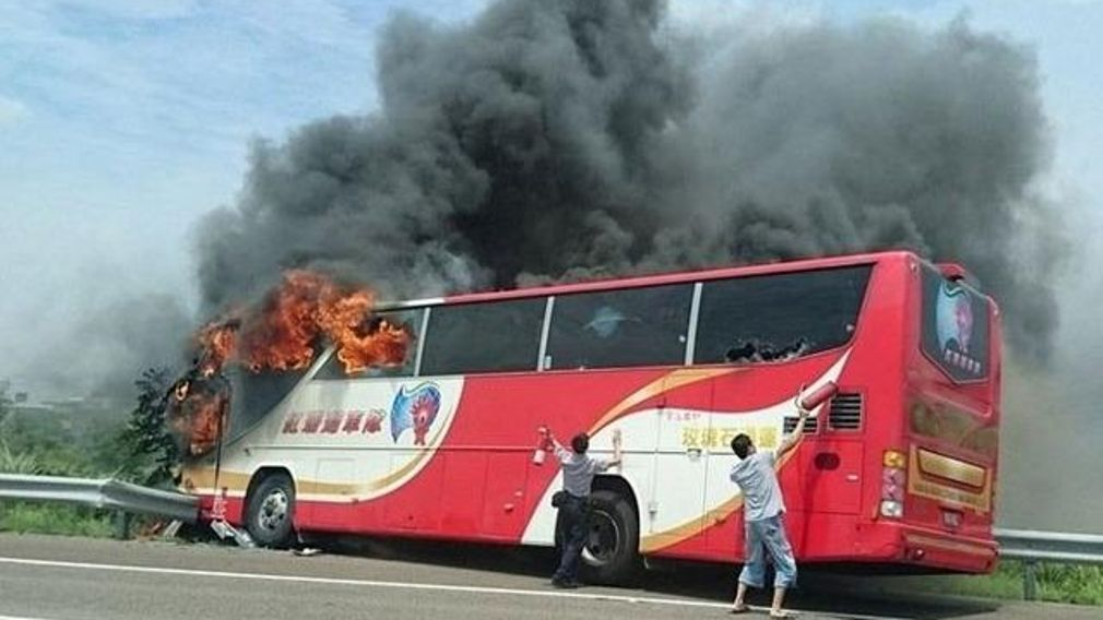 A tour bus in flames after it struck a railing on a highway in Taipei. (Photo: @XHNews on Twitter)